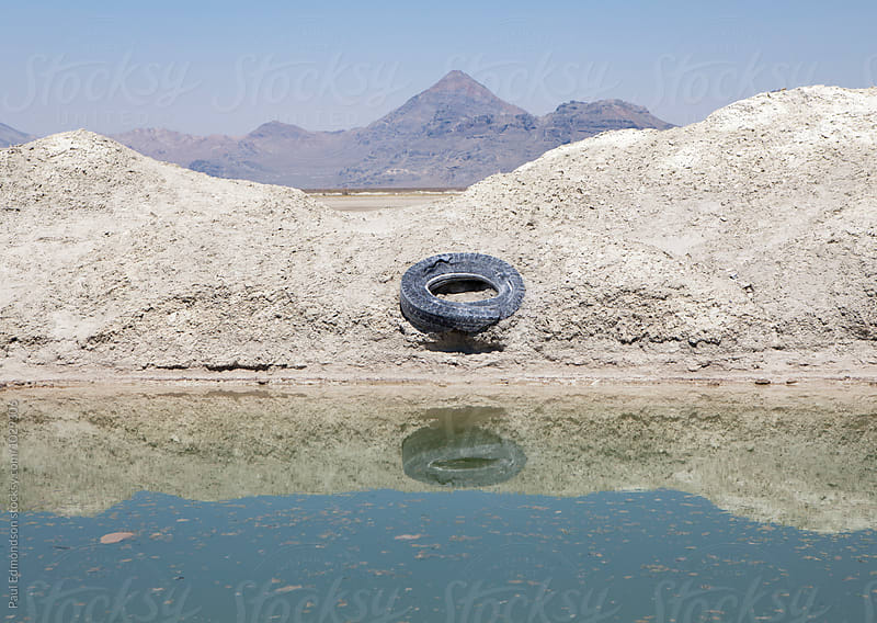 Discarded automobile tire along industrial canal and gravel pile by Paul Edmondson for Stocksy United