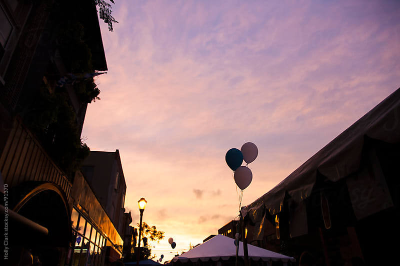 Three balloons float against an evening sky at a city festival. by Holly Clark for Stocksy United