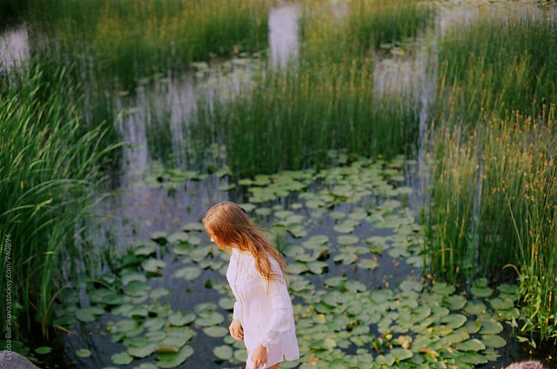 Woman among overgrown lake sedge by Liubov Burakova for Stocksy United