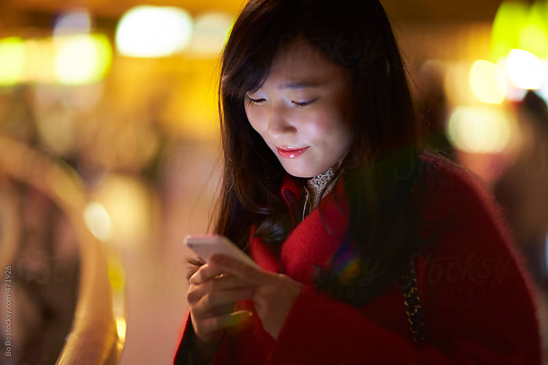 young asian woman using mobile phone in the street at night by Bo Bo for Stocksy United