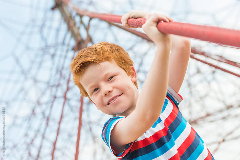 Boy playing on a climbing frame in a park by Craig Holmes for Stocksy United
