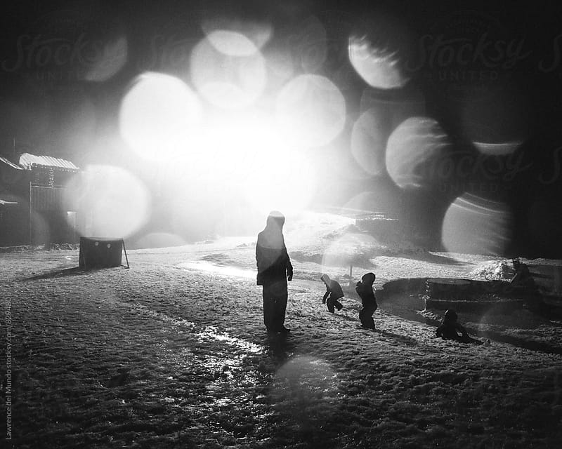 Silhouette of Mother and her Sons playing in the snow at night by Lawrence del Mundo for Stocksy United
