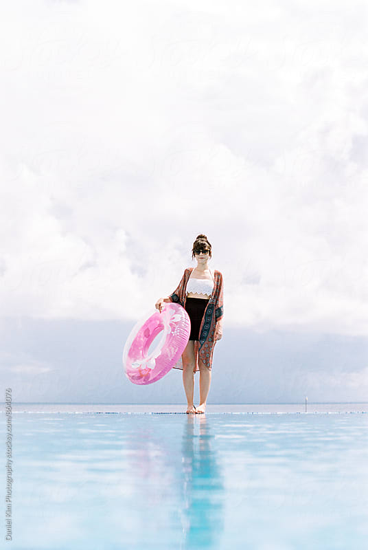 Woman standing on infinity pool by Daniel Kim Photography for Stocksy United