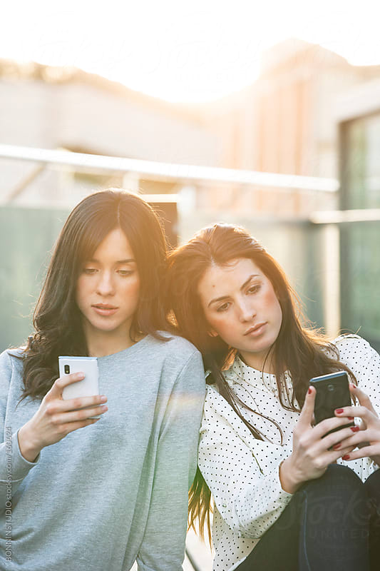 Two young girlfriends with smartphone sitting together in outdoors. by BONNINSTUDIO for Stocksy United