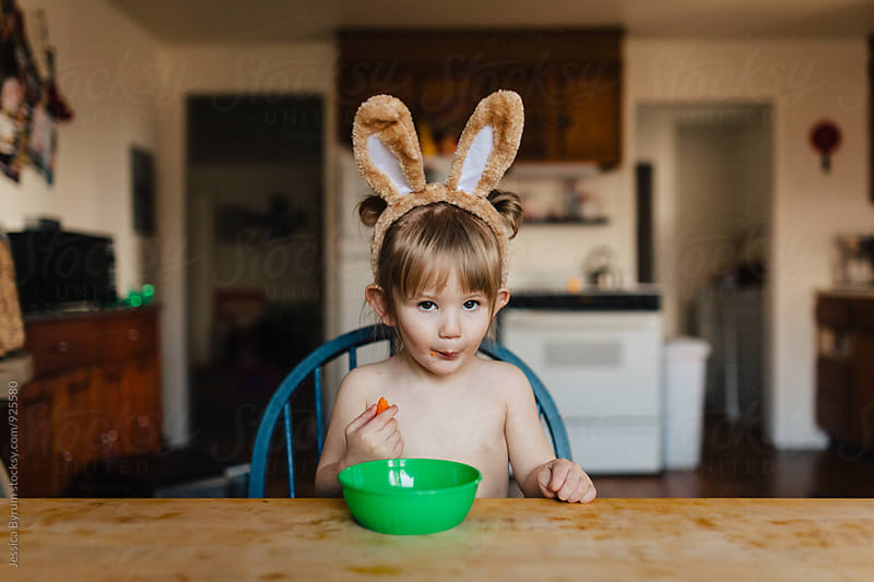Young toddler child in bunny ears eating baby carrots at the kitchen table. by Jessica Byrum for Stocksy United