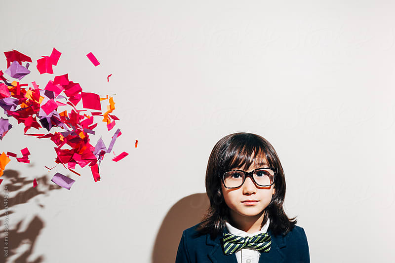 Serious young boy with with colorful confetti coming towards him by Kelli Seeger Kim for Stocksy United