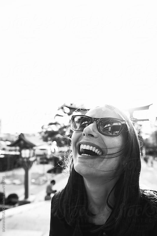 Portrait of a woman laughing outside. Black and white photo.  by BONNINSTUDIO for Stocksy United
