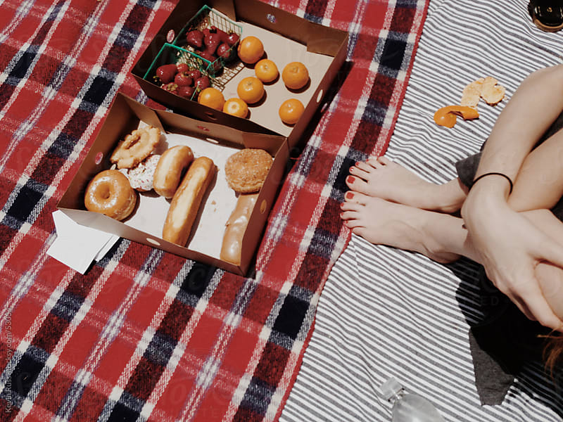 Woman Sits at a Donut and Fruit Picnic by Kevin Russ for Stocksy United