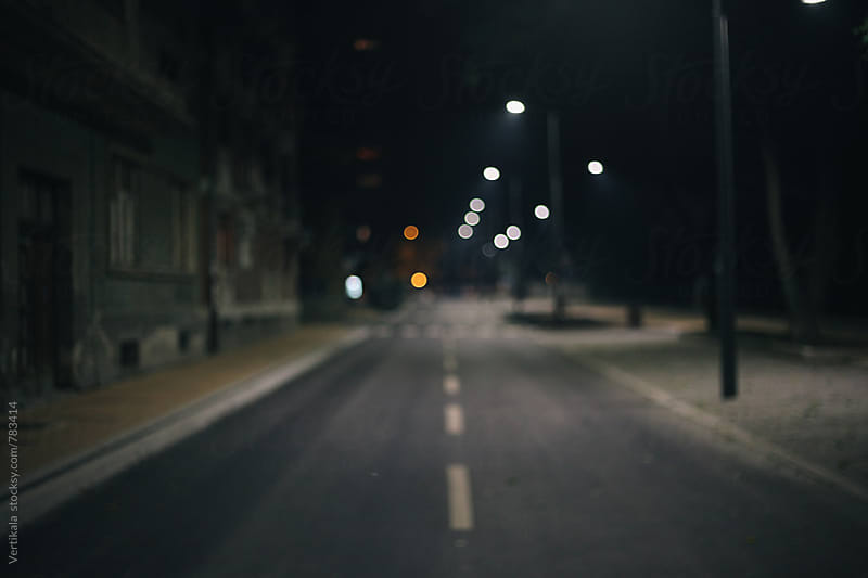 Empty street during the night. Blurry.  by VeaVea for Stocksy United