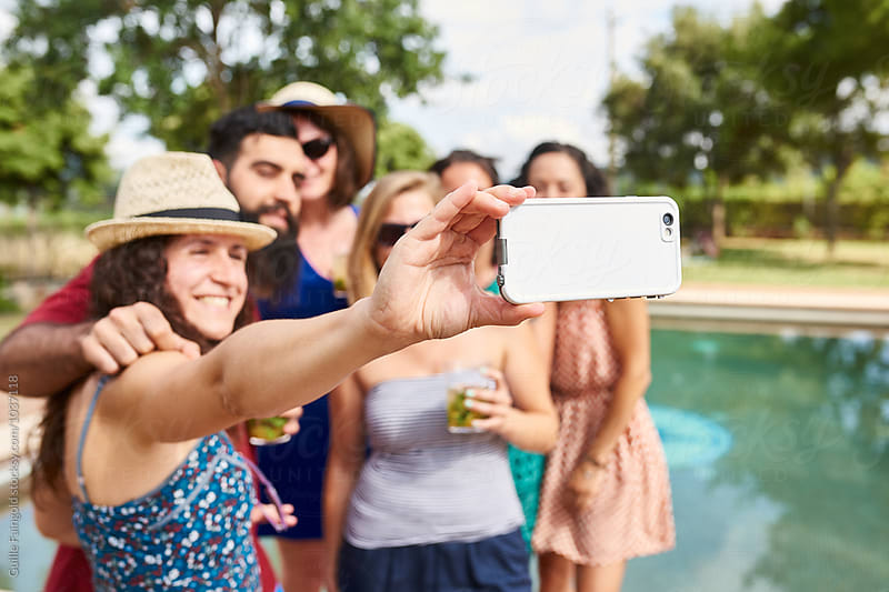 Smiling friends taking selfie with cell phone at pool by Guille Faingold for Stocksy United