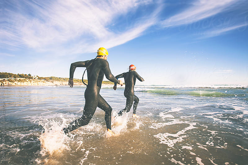 Two triathletes running to the water on triathlon race. by BONNINSTUDIO for Stocksy United