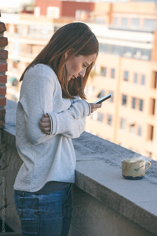 Young woman with smartphone in the terrace. She has cold. by BONNINSTUDIO for Stocksy United