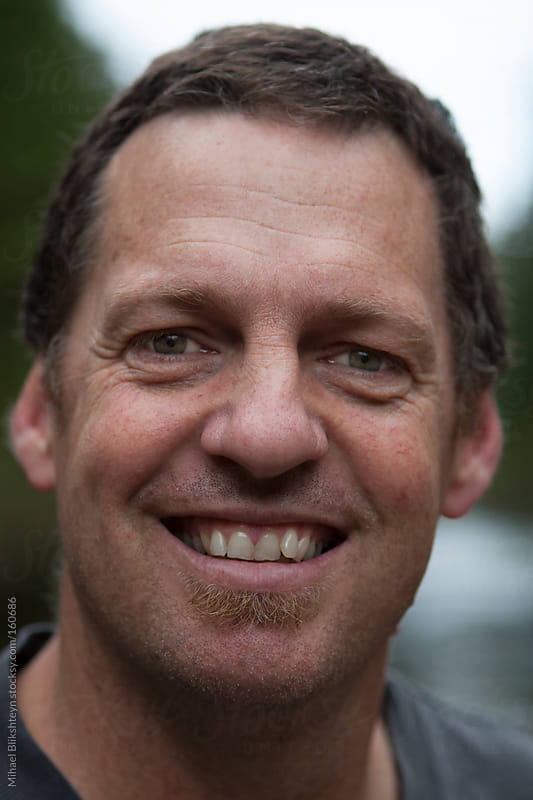 Closeup of a smiling middle-aged man's face by Mihael Blikshteyn for Stocksy United