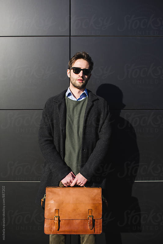 Portrait of business man holding a briefcase by michela ravasio for Stocksy United