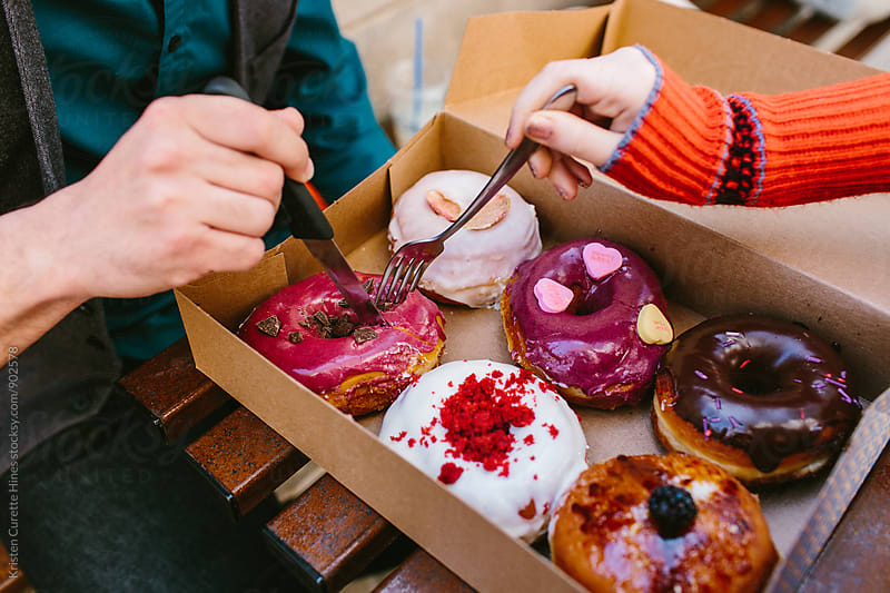 A man and woman sharing a box of donuts by Kristen Curette Hines for Stocksy United
