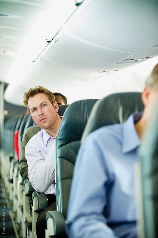 Airplane: Concerned Passenger Looks Down Aisle by Sean Locke for Stocksy United