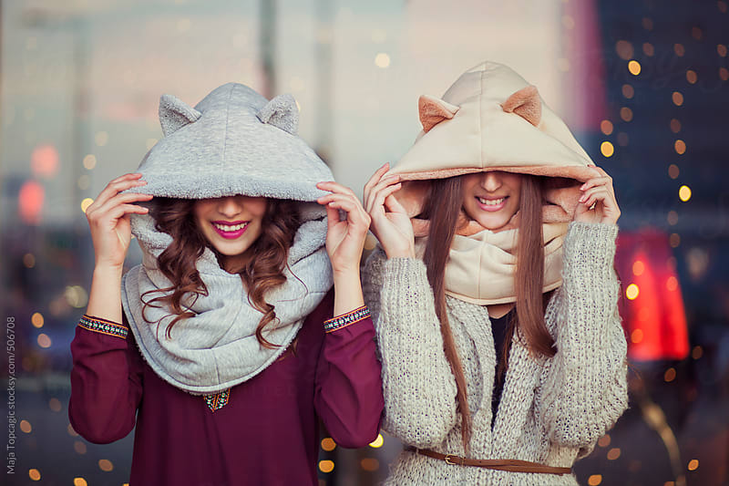 Two girls with cat hats laughing by Maja Topcagic for Stocksy United