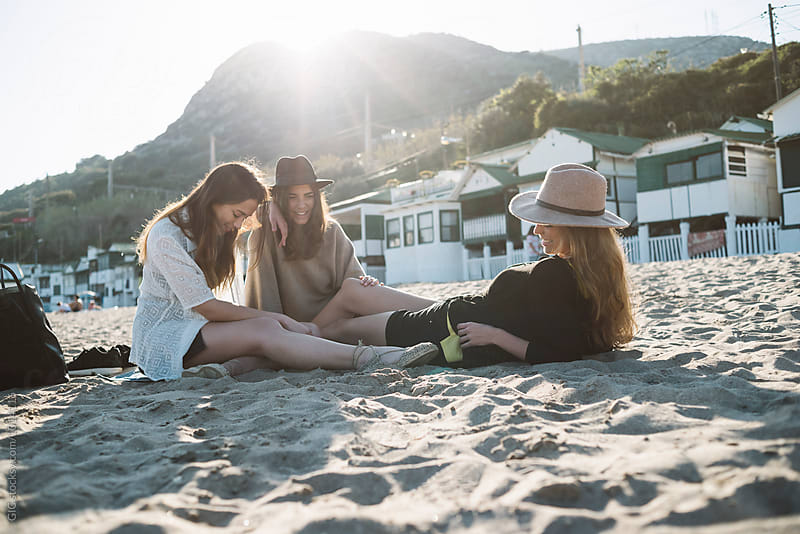 Young women relaxing at the beach at sunset by Simone Becchetti for Stocksy United