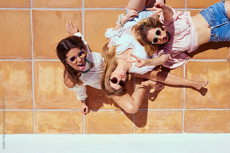 Three friends making faces and gesturing on stone floor in sunlight by Guille Faingold for Stocksy United