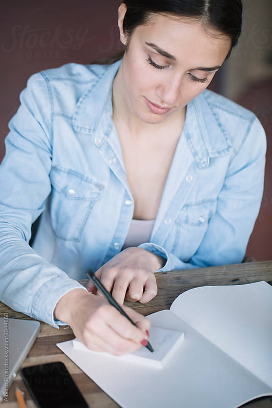 Brunette in denim jacket writing notes by Alberto Bogo for Stocksy United