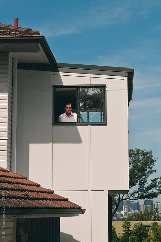 man looking out of window by Gillian Vann for Stocksy United