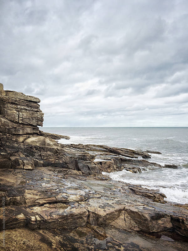 Stormy waves hitting a rocky shoreline by James Ross for Stocksy United