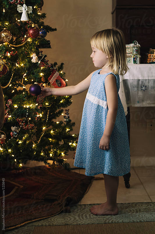 Little Girl Standing by Christmas Tree by Stephen Morris for Stocksy United