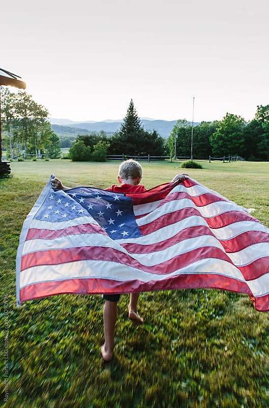 Child holding American Flag while running by Raymond Forbes LLC for Stocksy United