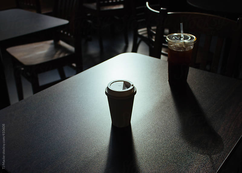 A paper coffee cup sits on a table in a dark room by TJ Macke for Stocksy United