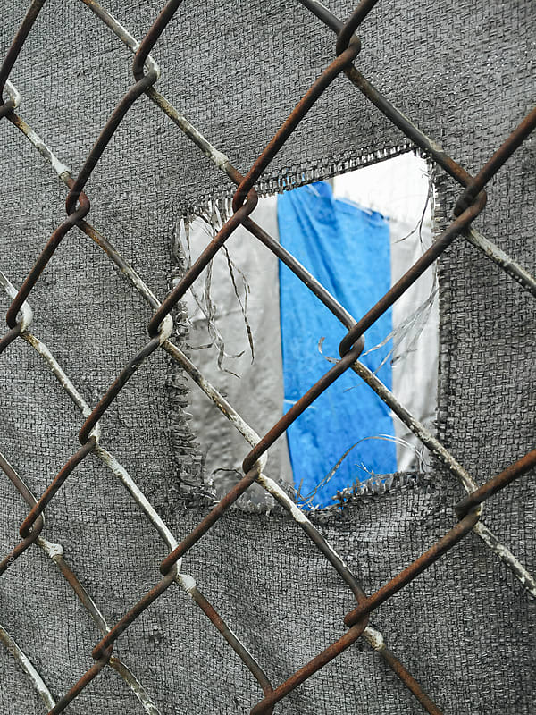 Close of chain-link fence, view through hole in tarp  by Paul Edmondson for Stocksy United