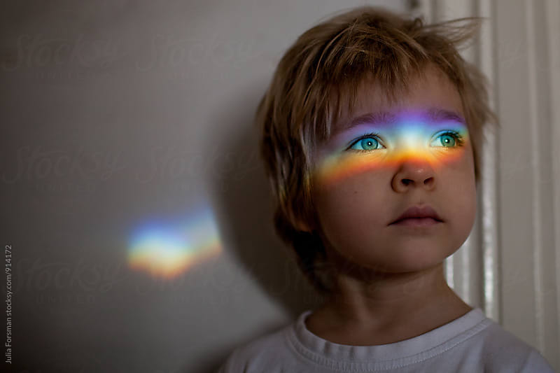 Little girl with a rainbow of light across her eyes. by Julia Forsman for Stocksy United