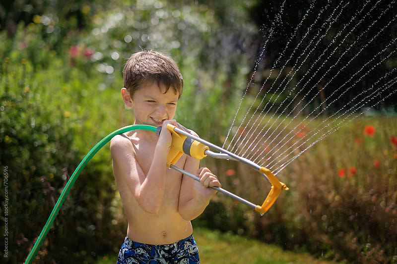 Child having fun with a water sprinkler by Rebecca Spencer for Stocksy United