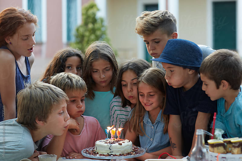 Group of children blowing the candles of a birthday cake by Miquel Llonch for Stocksy United