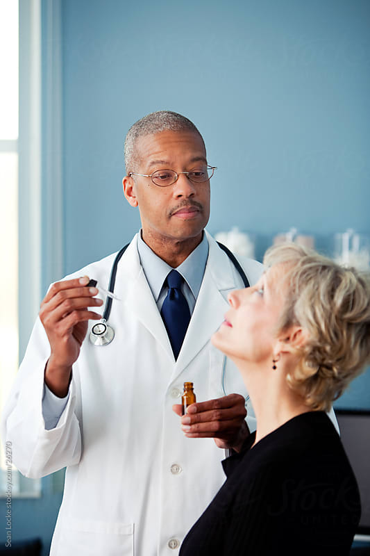 Exam Room: Doctor Ready to Administer Eye Drops to Mature Woman by Sean Locke for Stocksy United