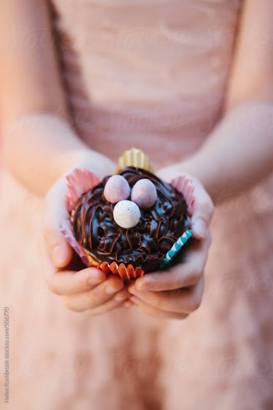 Hands holding an Easter cupcake by Helen Rushbrook for Stocksy United