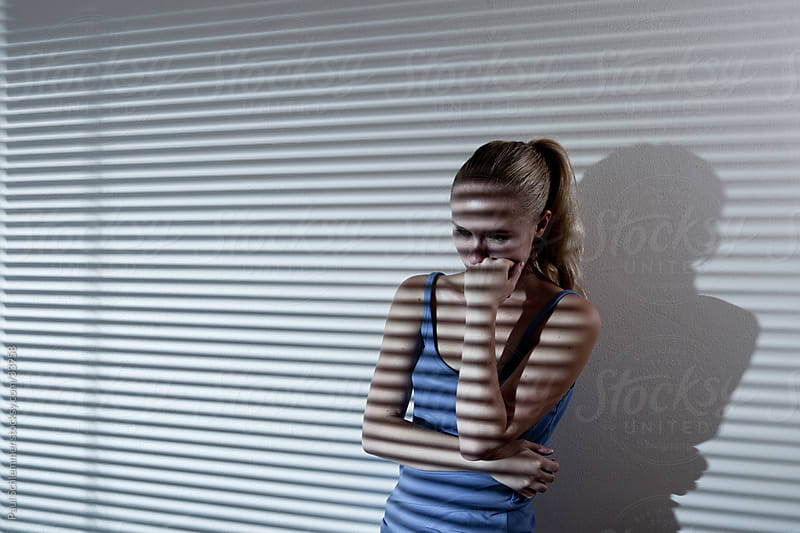 Depressed young woman in a moody stripe light by Paul Schlemmer for Stocksy United