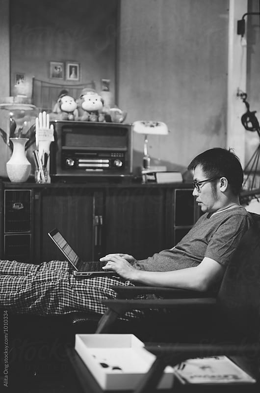 Asian man working remotely from home by Alita Ong for Stocksy United