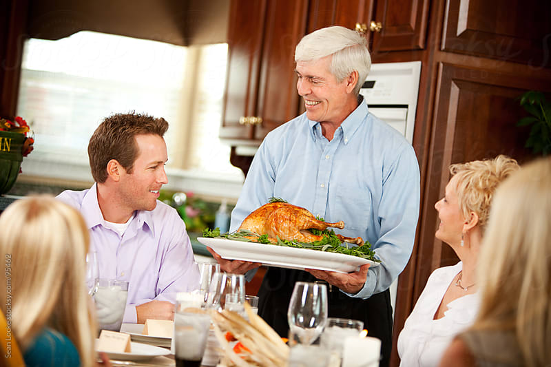 Thanksgiving: Grandfather Brings Roast Turkey to Table by Sean Locke for Stocksy United