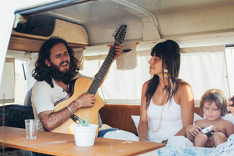 On The Road - Hippie Family of Three Playing and Listening to Music in Camper Van by Julien L. Balmer for Stocksy United