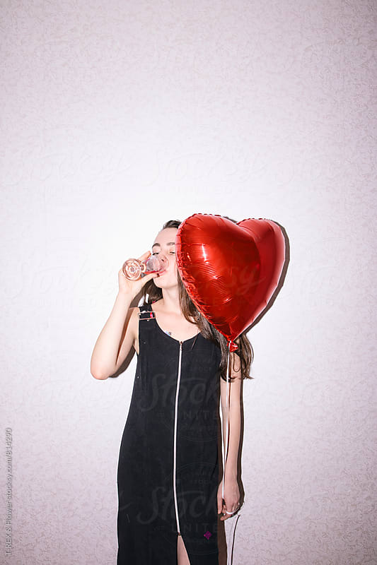 Young brunette woman drinking champagne and holding red balloon by T-REX & Flower for Stocksy United