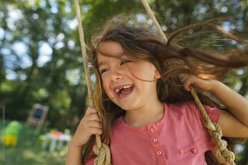 Happy child swinging. by Dejan Ristovski for Stocksy United