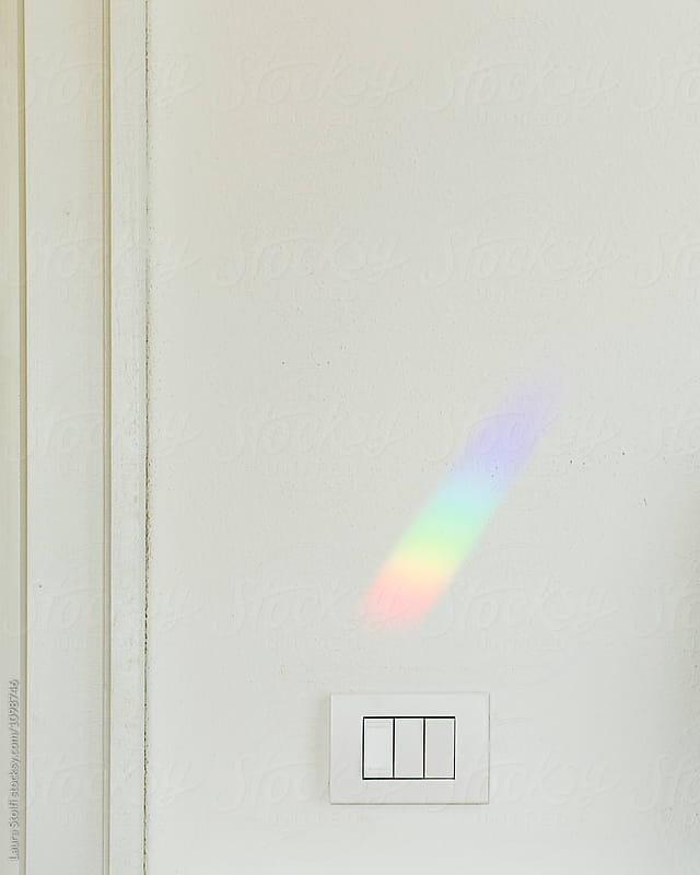Rainbow shining on wall above light switches by Laura Stolfi for Stocksy United