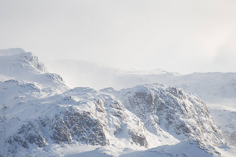 Snow is blowing from a mountain peak by Jonas Räfling for Stocksy United