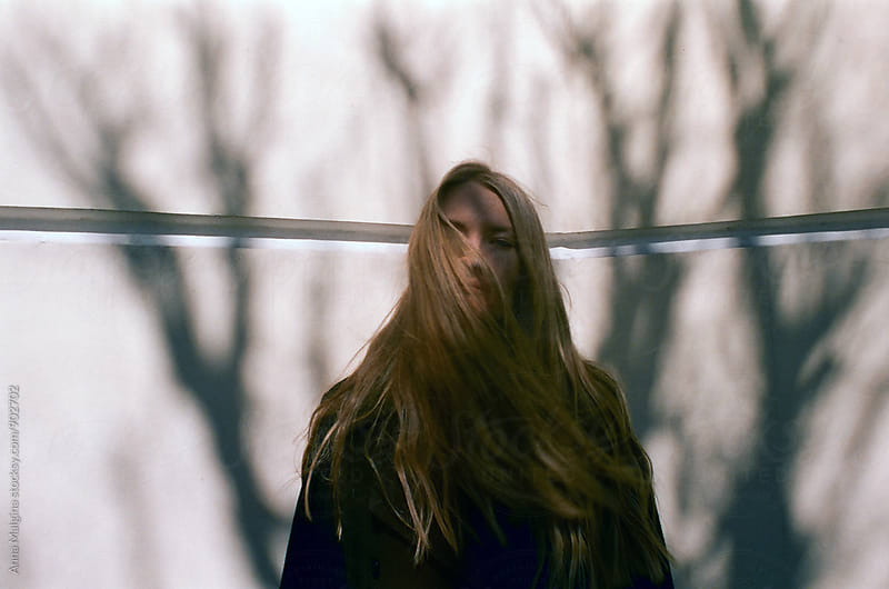 A film photo of young beautiful blond woman standing in the shadow of tree by Anna Malgina for Stocksy United