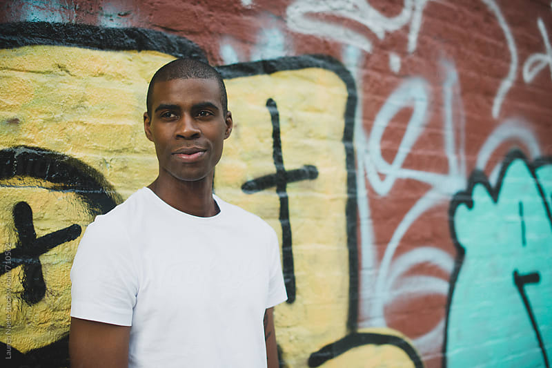 Young man in white t-shirt in the city by Lauren Naefe for Stocksy United