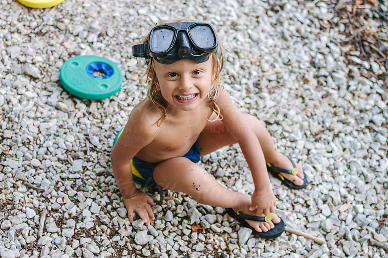 smiling cute toddler with diving goggles sitting on a rocky beach looking up into the camera by Leander Nardin for Stocksy United