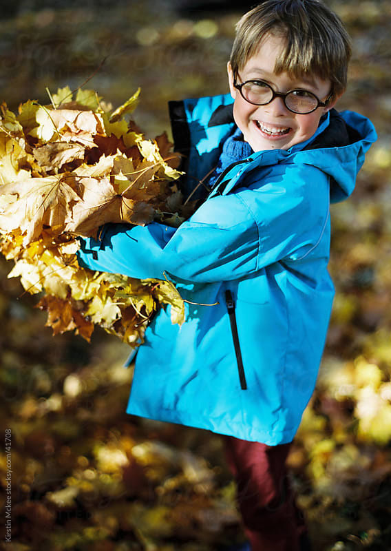 Smiling boy wearing glasses holding autumn leaves in fall by Kirstin Mckee for Stocksy United