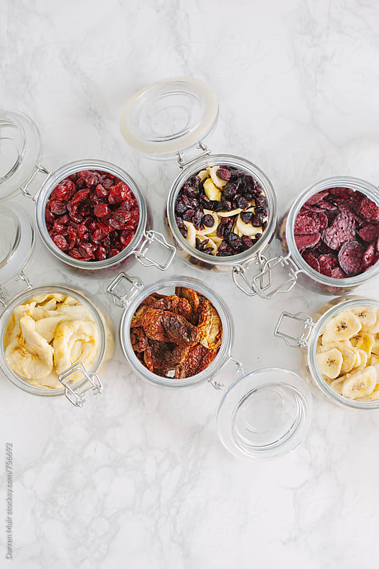 Dehydrated vegetables and fruits in glass jars,seen from above. by Darren Muir for Stocksy United