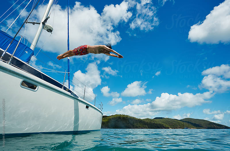 Young male jumps out of a boat by Joaquim Bel for Stocksy United