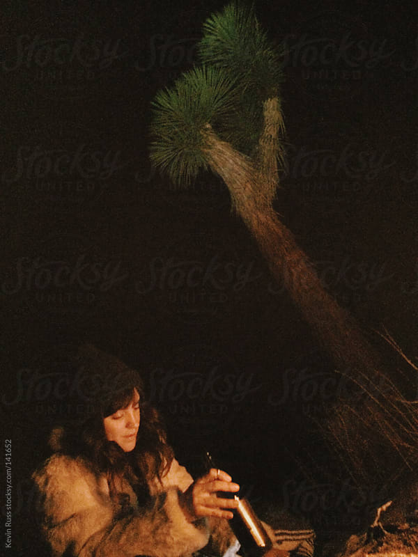 Woman Drinking Beer by Campfire at Joshua Tree by Kevin Russ for Stocksy United
